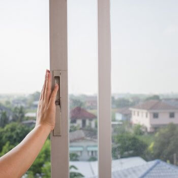womans hand on a sliding window opening it
